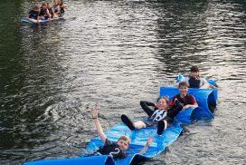 Kinder auf Matte im Wasser
