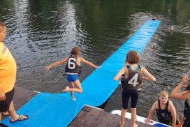 Kind läuft über Matte im Wasser